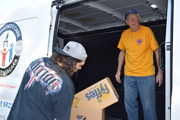 Lion John Burton unloads some boxes with the help of Noah Bennett.