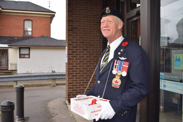 Barry Stark canvassing poppies at an Ontario St. storefront in Beamsville