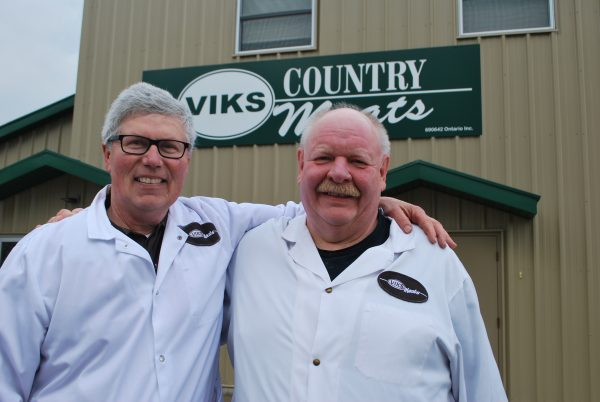 Two men stand infront of a sign for Vik's Country Meat.