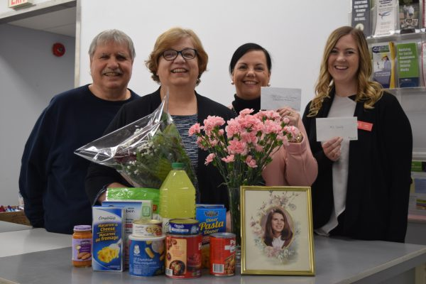 Four people stand behind a collection of flowers, donated food and a framed photo of Christina.
