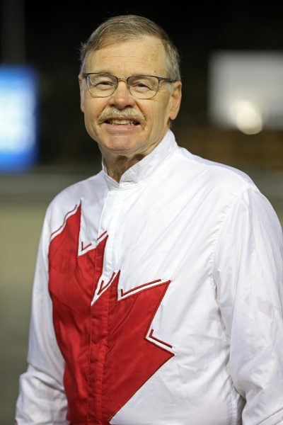A man wearing glasses and a white riding jacket with a red maple leaf on it smiles at the camera.