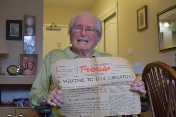 """An elderly lady holds up a Dutch newspaper with a headline in English that reads: """"A Welcome to our Liberators""""."""