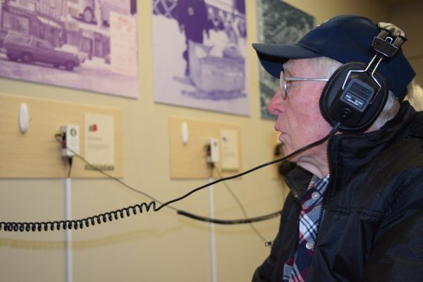 An older man wears headphones while reading text for a museum exhibit that the headphones are attached to.
