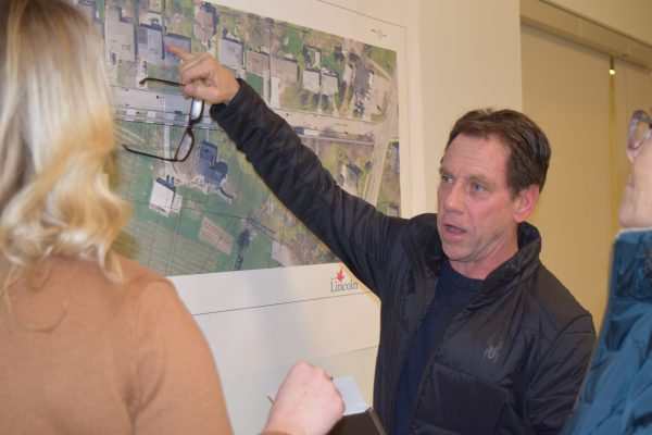 A man points to a map that details plans for road reconstruction.