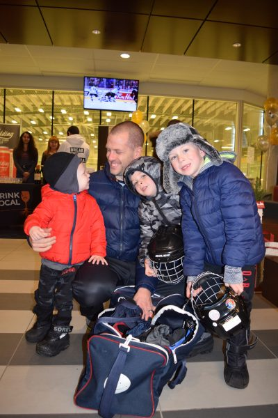 Dad and his three boys get skating equipment on.