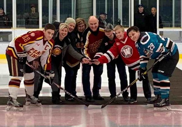 Six people stand while holding a single puck flanked two hockey players.