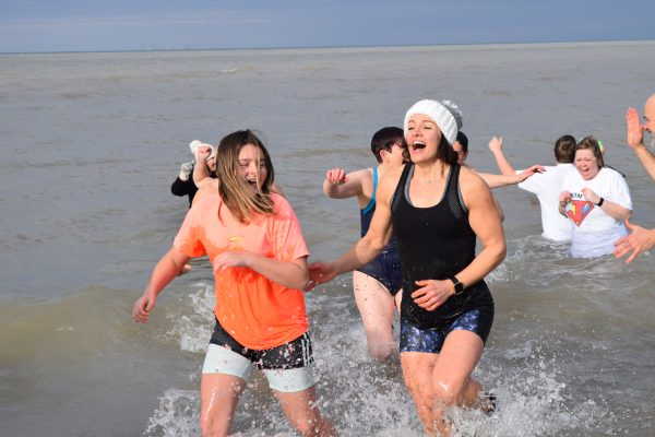 Two girls hurriedly run out of Lake Ontario while laughing,