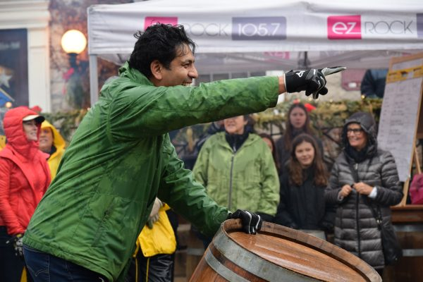 A man smileswhile pointing away from the camera and resting his other hand on the top of a wine barrel.