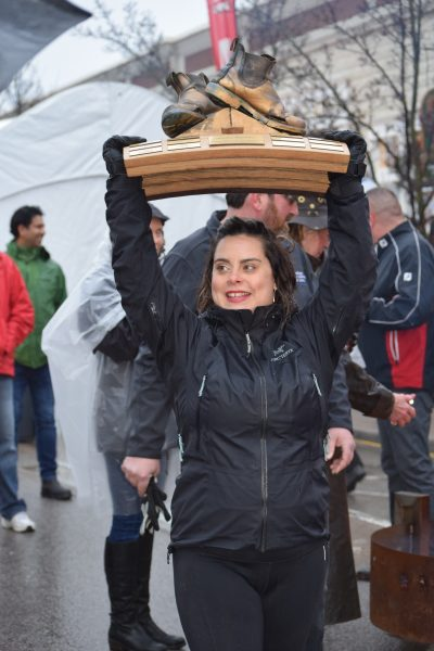A woman holds a trophy high above her head.