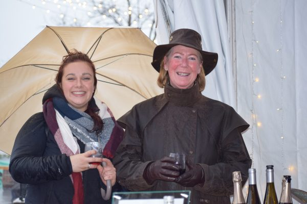 Two women stand under a tent holding on to wine glasses, the one on the left also holding an umbrella.