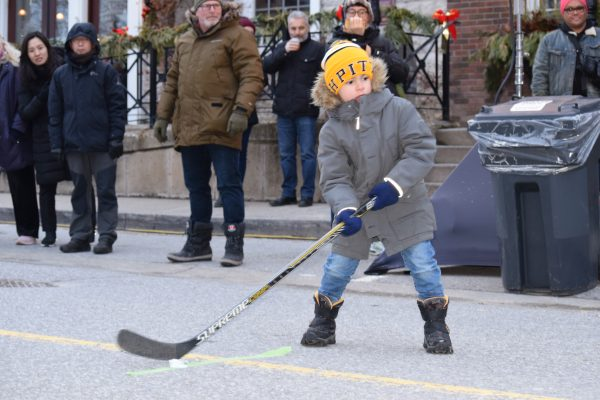 A young boy swings his hockey stick to hit a puck made out of ice.