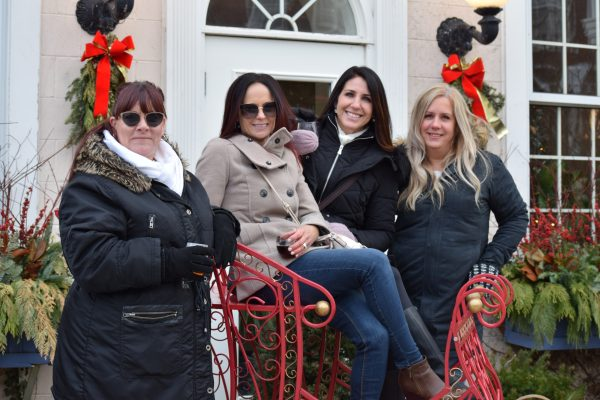Four women pose together on a bench made to look like a sleigh.