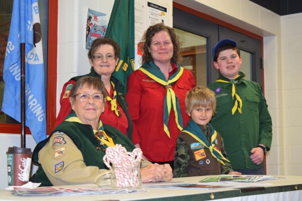 Three scout leaders and two scouts stand near the flag.