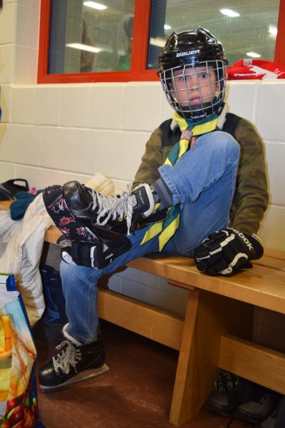 A beaver scout lace up his skates looks into the picture with a startled look on his face.
