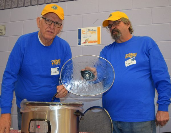 Two men in Lions Club uniforms stand next to a chili pot.