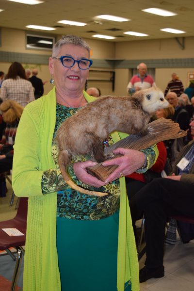A middle-age woman with close-cropped white hair, blue rim glasses and a green outfit smile while holding a stuffed opossum.