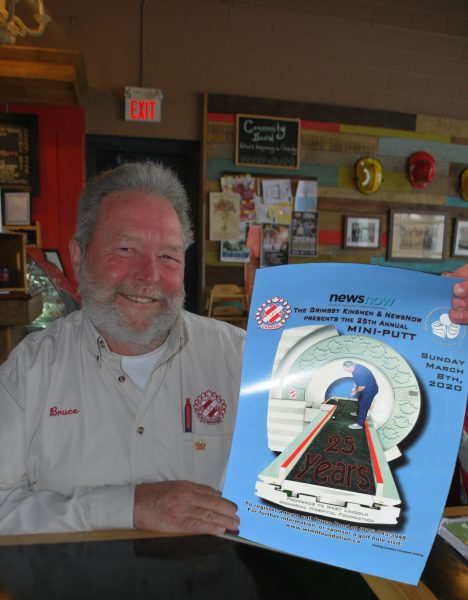 A man smiles while holding a poster detailing the upcoming kinsmen mini-putt tournament.