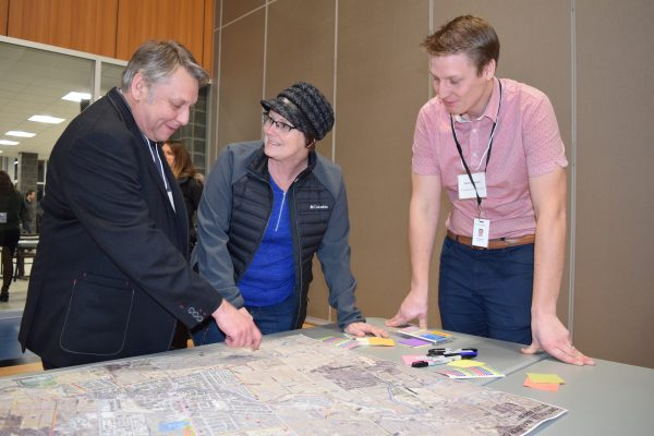 Three people stand around a large map of Smithville, which sits on a table. The man to the left point at the map.