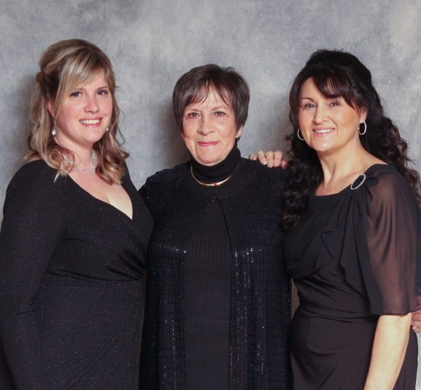 Three ladies in black dresses pose together while smiling.
