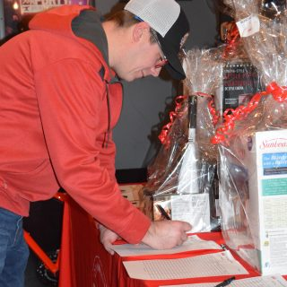 A man in a red jacket writes down his id for a silent auction item.