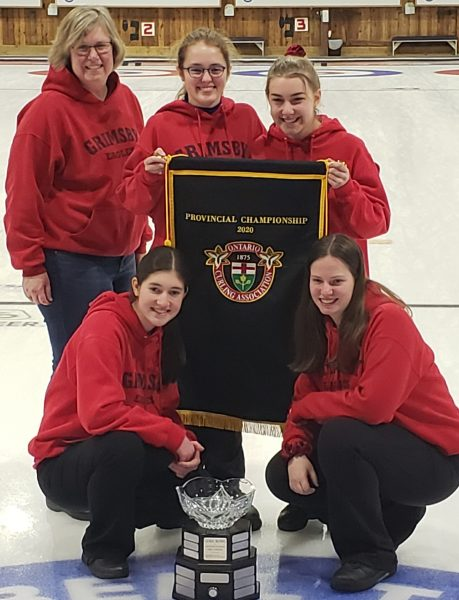 Four girls and their curling coach stand with their champions pendant and trophy.