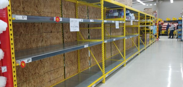 Several metres of grocery shelving that are bare, except for a sign asking customer not to buy more than two packages of toilet paper.