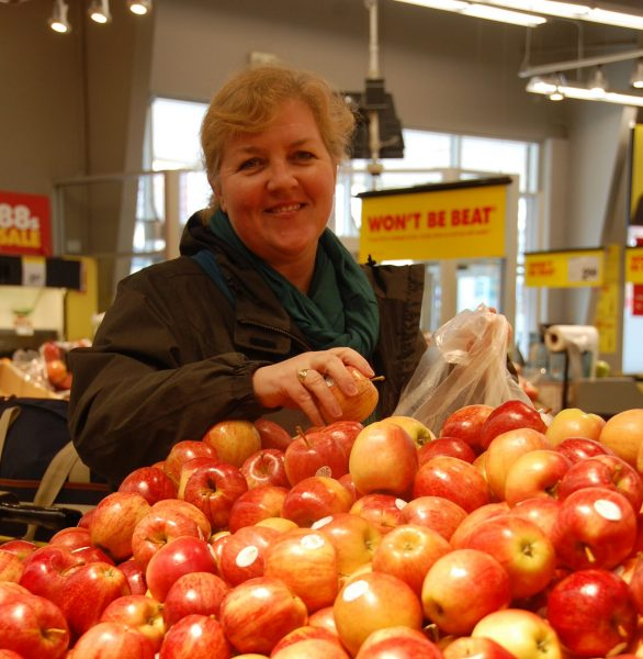A woman smiles from accross a grocery aisle of apples.