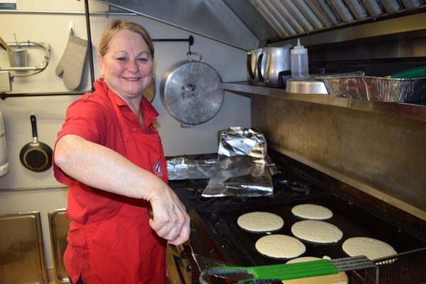 A woman smiles while flipping pancakes on a grill.