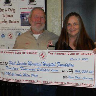 A man and a woman hold a giant cheque for $14,000.