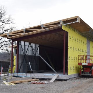 A building that's still under contruction with exposed insulation and a steel roof.
