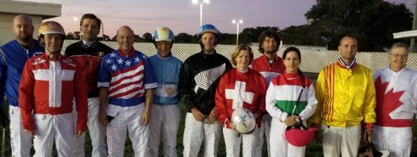Eleven horse race driver wearing outfits bearing their national flag stand in a row.