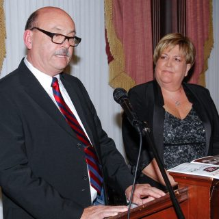 A man speaks at a podium while a woman looks at him from the right.