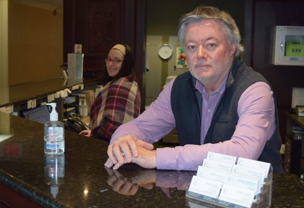 A man in a pink suit and blue vest sits behind a bar, as a woman in the background in plaid pours a drink from the bar tap.