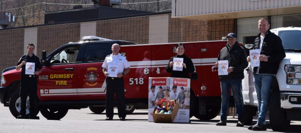 Five individuals stand 2 metres apart in front of a fire truck and a food drive box bearing the logo of the Grimsby Benevolent Fund.