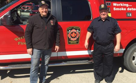 Two firefighters in casual uniform stand in front of a fire truck.