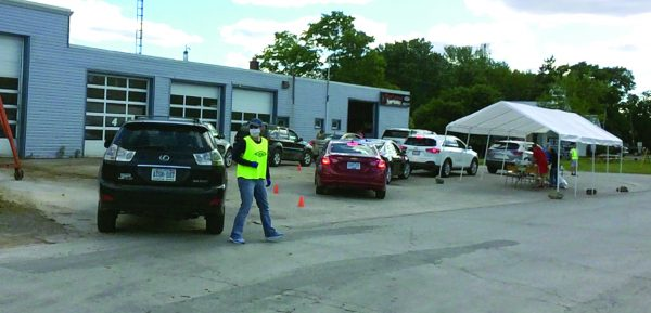 A man in a flourescent vest directs cars into a drive through barbecue.