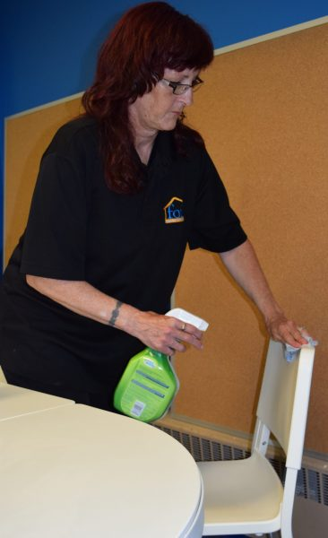 A woman sanitizes a chair using wipes and a spray bottle.
