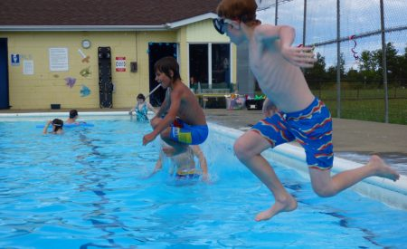Three kids jump into an outdoor pool.