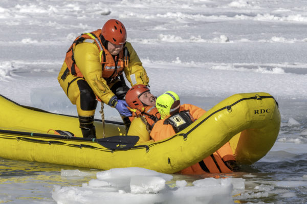A firefighter in an inflatable dingy pulls up a mannikin from icy Lake Ontario.