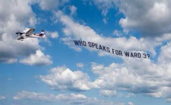 "A plane flying in the sky has a sign trailing behind it that reads: ""Who speaks for Ward 3?"""